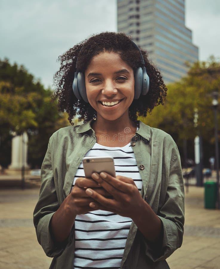 Mujer joven que escucha la música usando el teléfono elegante a través del auricular fotografía de archivo libre de regalías