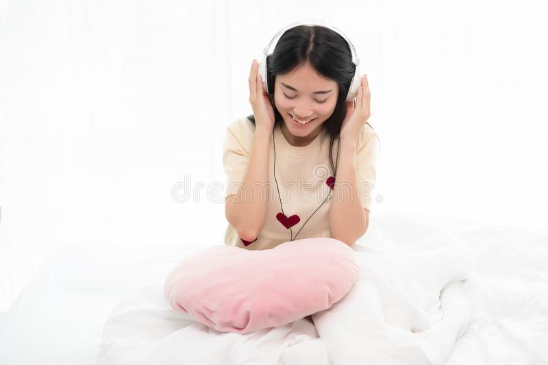 Mujer joven que escucha la m?sica en auriculares en cama fotos de archivo