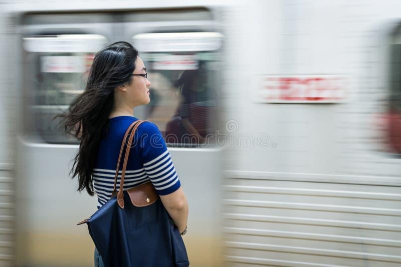 Mujer joven que espera en la estación de metro imagen de archivo