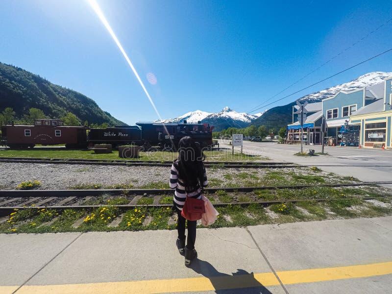 Mujer joven que espera en una plataforma del tren imagenes de archivo