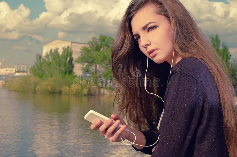 Mujer joven que espera su llamada Vistiéndose en un desgaste negro, una señora caucásica joven está haciendo una pausa el río, so imagen de archivo libre de regalías