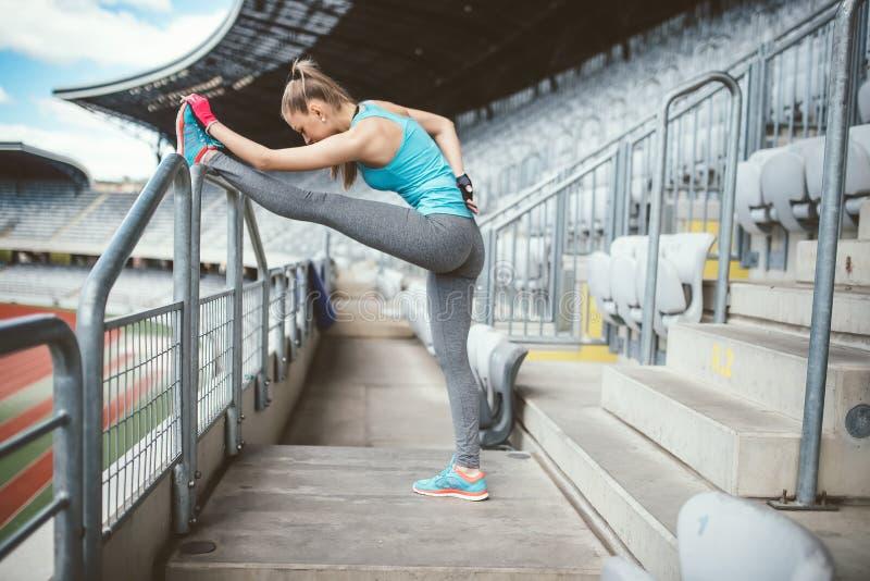 Mujer joven que estira al aire libre y que hace ejercicios del calentamiento Entrenando y resolviendo a concepto de la deportista fotografía de archivo