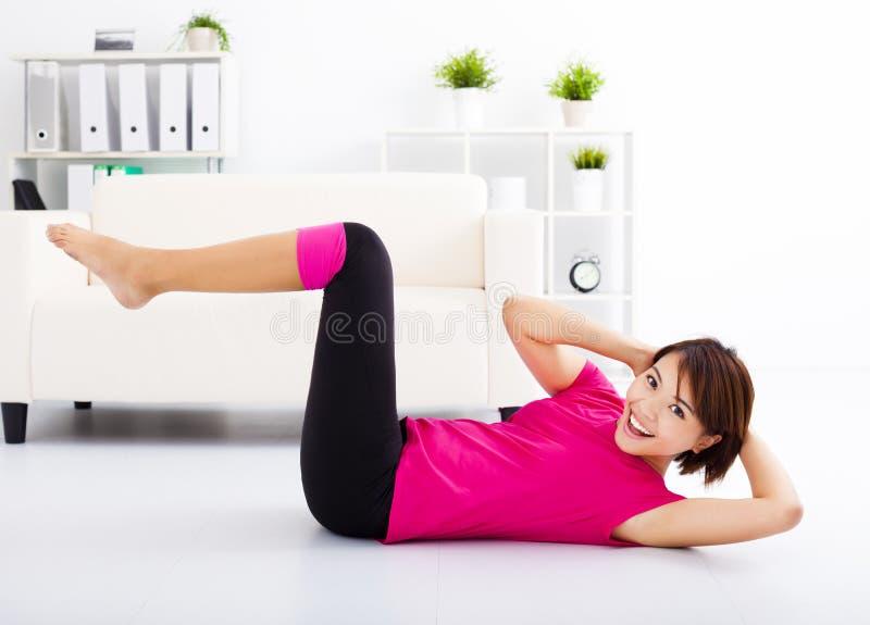 Mujer joven que estira en el piso foto de archivo libre de regalías