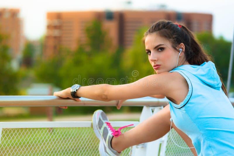 Mujer joven que estira las piernas en parque soleado foto de archivo