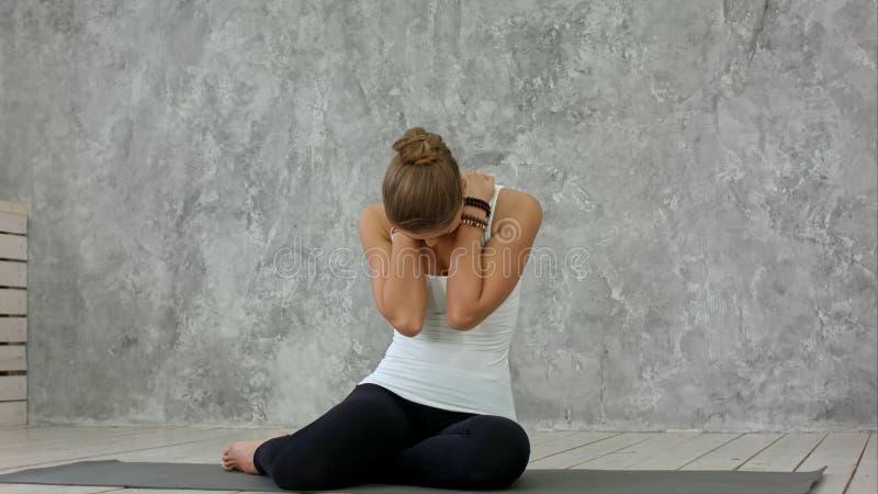 Mujer joven que estira su cuello y que mira lejos después de clase de la yoga foto de archivo