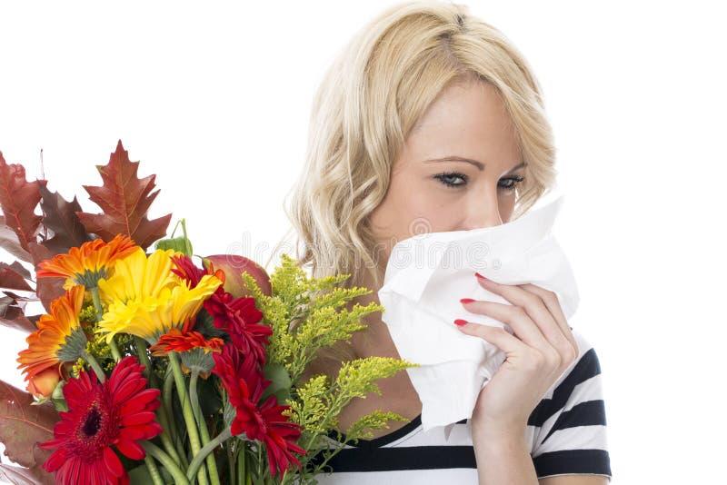 Mujer joven que estornuda de la alergia de la fiebre de heno que lleva a cabo un manojo de flores y de tejido foto de archivo libre de regalías