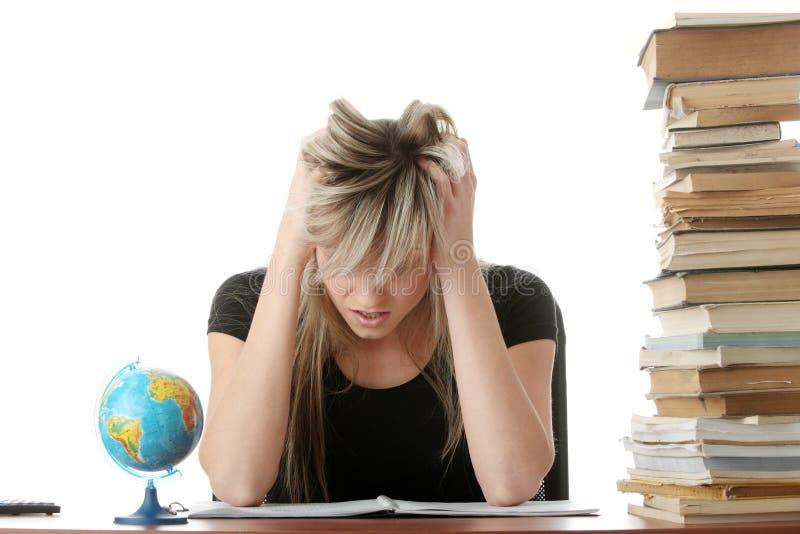 Mujer joven que estudia en el escritorio imagen de archivo libre de regalías