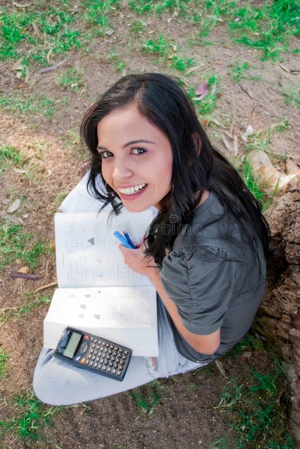 Mujer joven que estudia en el parque imagenes de archivo