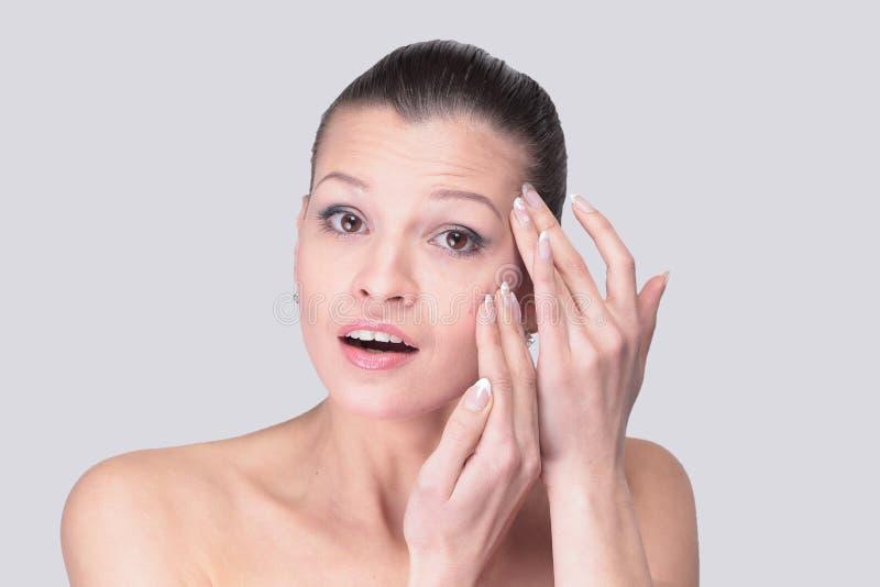 Mujer joven que examina su cara y arrugas que pueden aparecer, ISO foto de archivo
