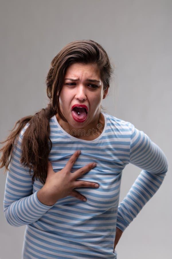 Mujer joven que expresa la repugnancia o el dolor fotos de archivo