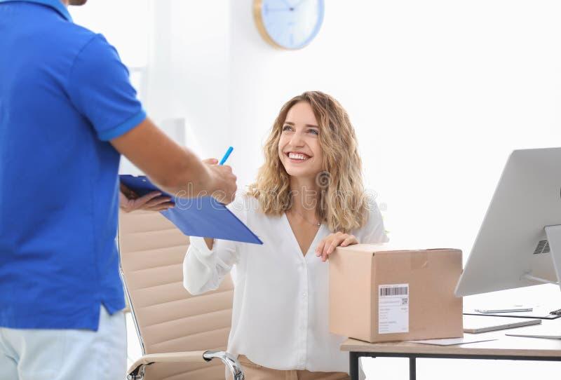 Mujer joven que firma para el paquete entregado en oficina imagen de archivo