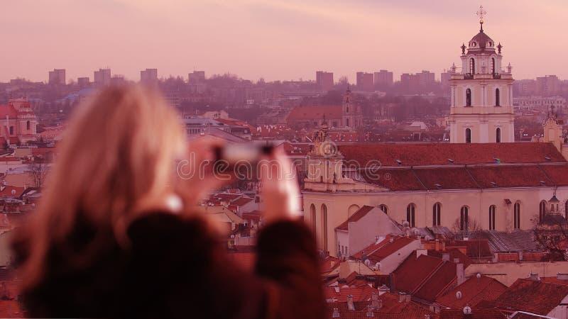 Mujer joven que fotografía la ciudad de Vilna foto de archivo libre de regalías