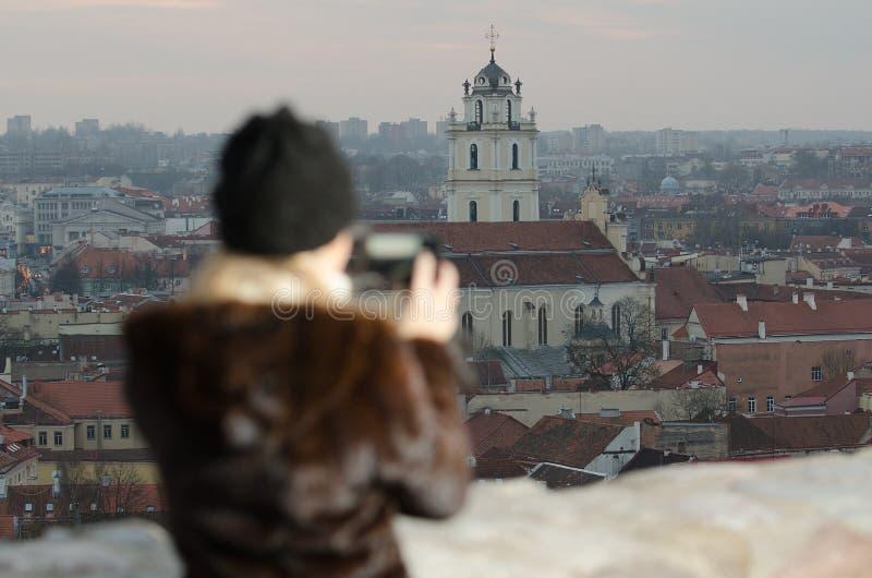 Mujer joven que fotografía la ciudad de Vilna imagen de archivo