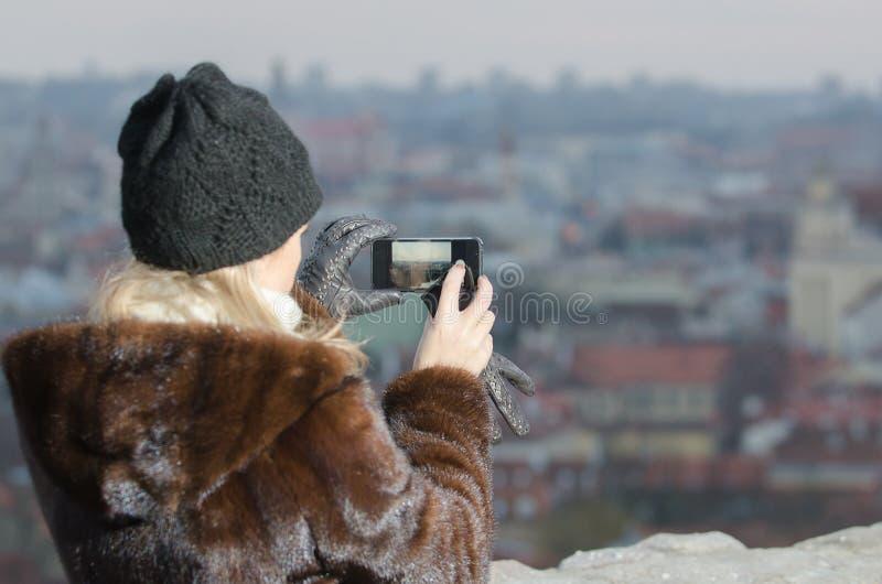 Mujer joven que fotografía la ciudad de Vilna fotos de archivo