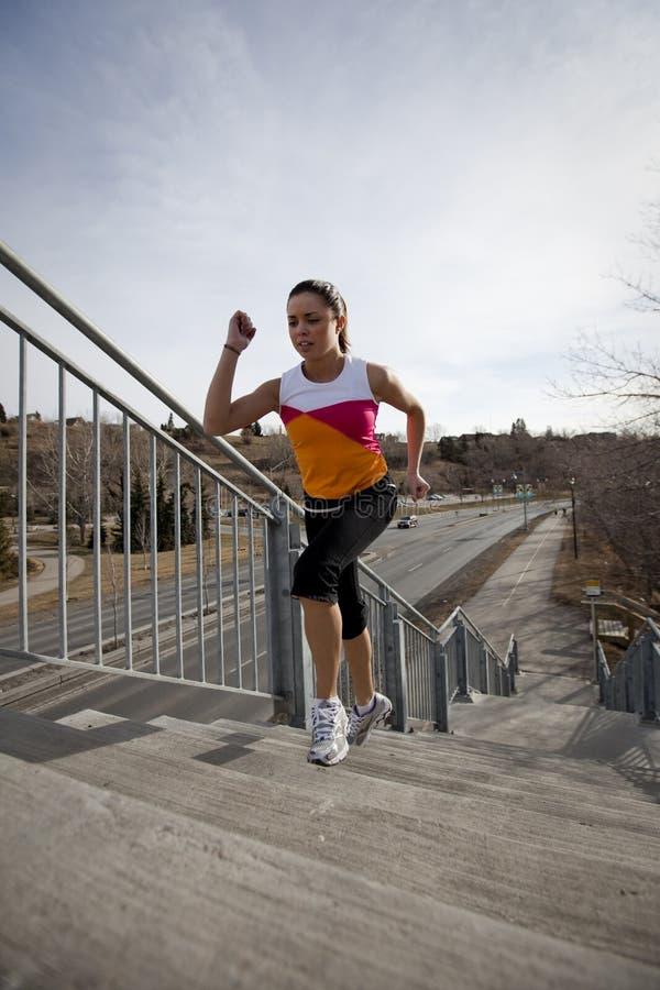 Mujer joven que funciona con para arriba las escaleras en ciudad. imagen de archivo libre de regalías