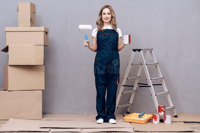 Mujer joven que funciona con a un pintor de casas Contratan a una mujer a pintar las paredes imagen de archivo