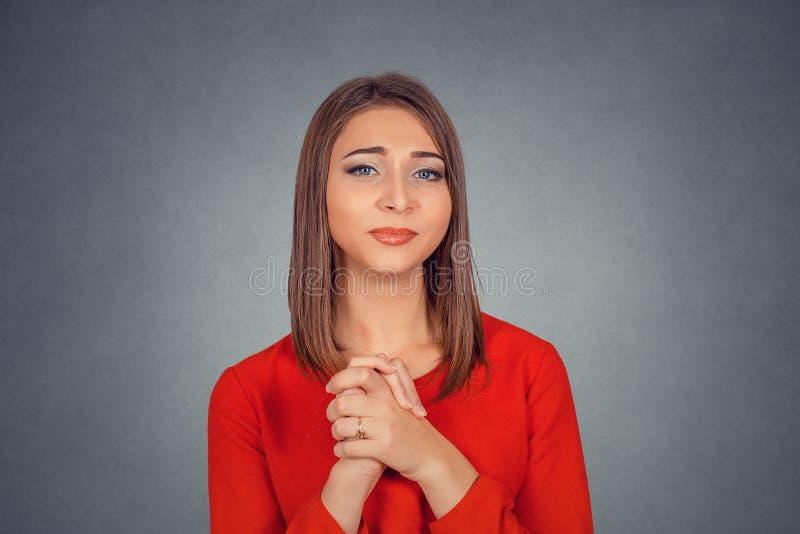 Mujer joven que gesticula con las manos abrochadas agradecidas imagenes de archivo