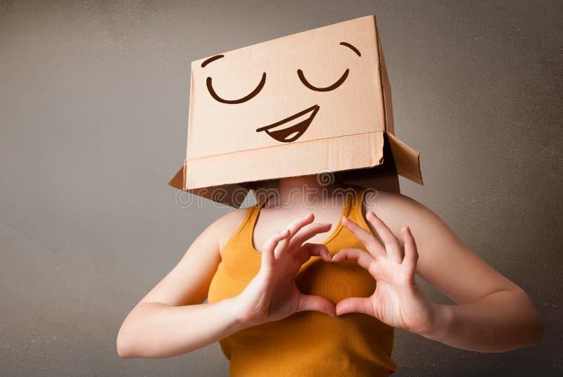 Mujer joven que gesticula con una caja de cartón en su cabeza con el smil imagen de archivo libre de regalías