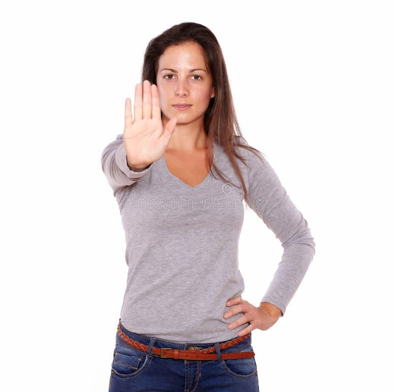 Mujer joven que gesticula la muestra de la mano de la parada imagen de archivo