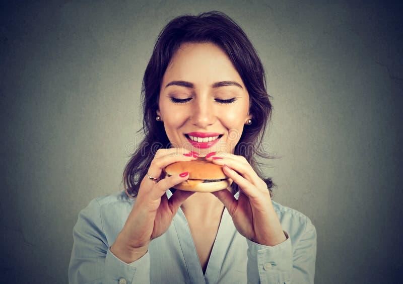 Mujer joven que goza de los alimentos de preparación rápida imagen de archivo