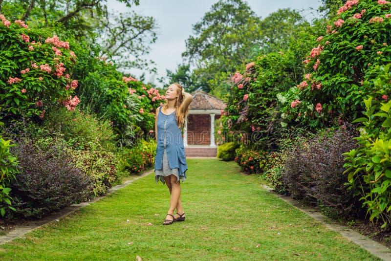 Mujer joven que goza de un jardín floreciente hermoso imágenes de archivo libres de regalías
