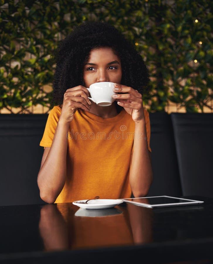 Mujer joven que goza del café en café imágenes de archivo libres de regalías