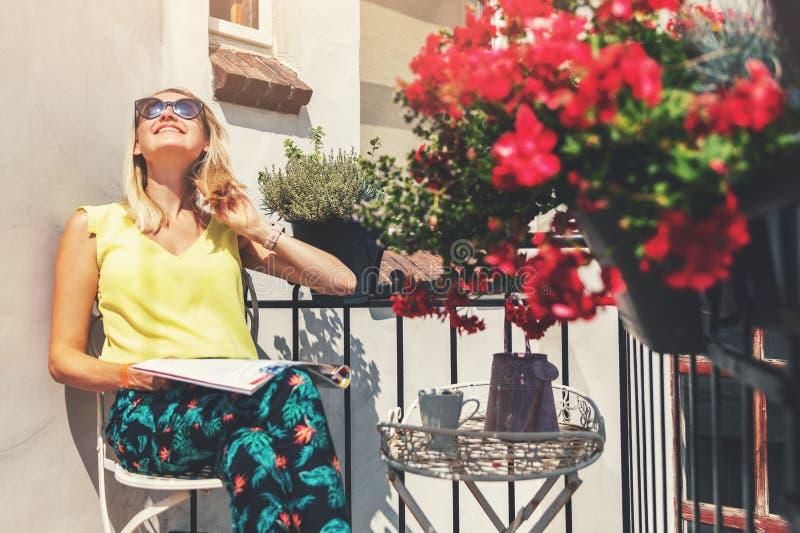 Mujer joven que goza del sol en balcón romántico con las cajas de la flor imagenes de archivo