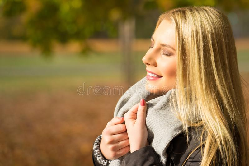 Mujer joven que goza del sol del otoño imagen de archivo libre de regalías