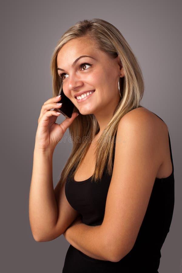 Mujer joven que habla en el móvil foto de archivo