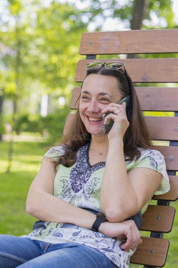 Mujer joven que habla en el smartphone y que r?e en el parque en la relajaci?n femenina hermosa del banco en un banco de parque y fotografía de archivo libre de regalías