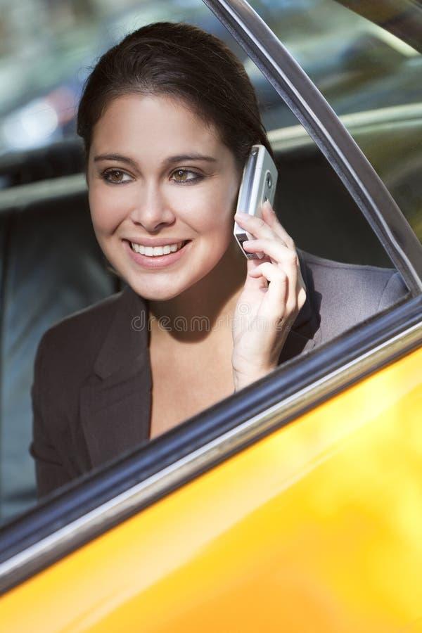 Mujer joven que habla en el teléfono celular en taxi amarillo fotos de archivo