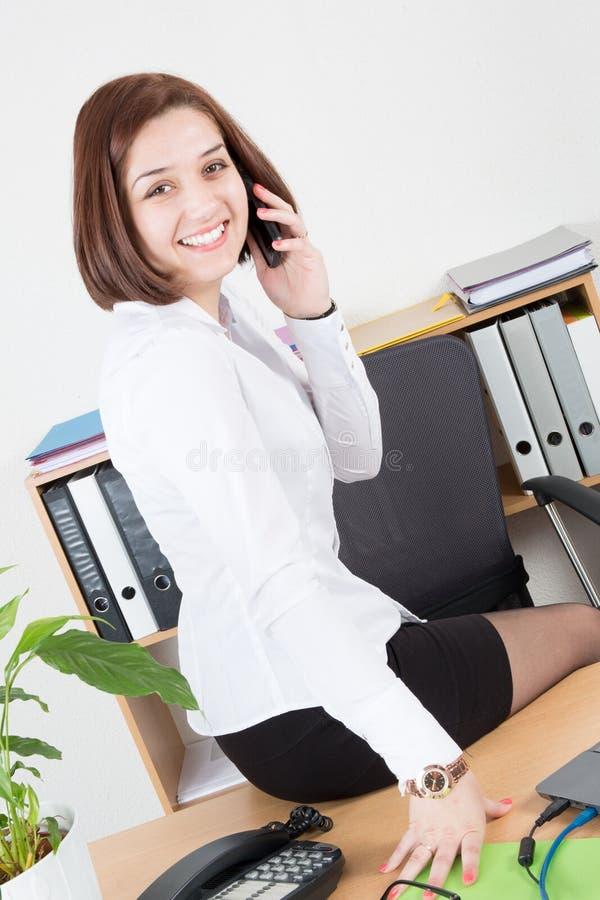 Mujer joven que habla en el teléfono móvil y que sonríe mientras que se sienta en su lugar de trabajo en oficina foto de archivo