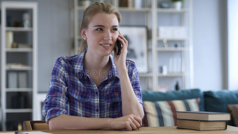 Mujer joven que habla en el teléfono mientras que se relaja en silla fotos de archivo libres de regalías