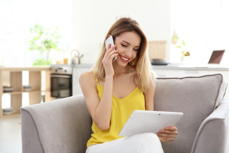 Mujer joven que habla en el teléfono mientras que usa la tableta fotografía de archivo