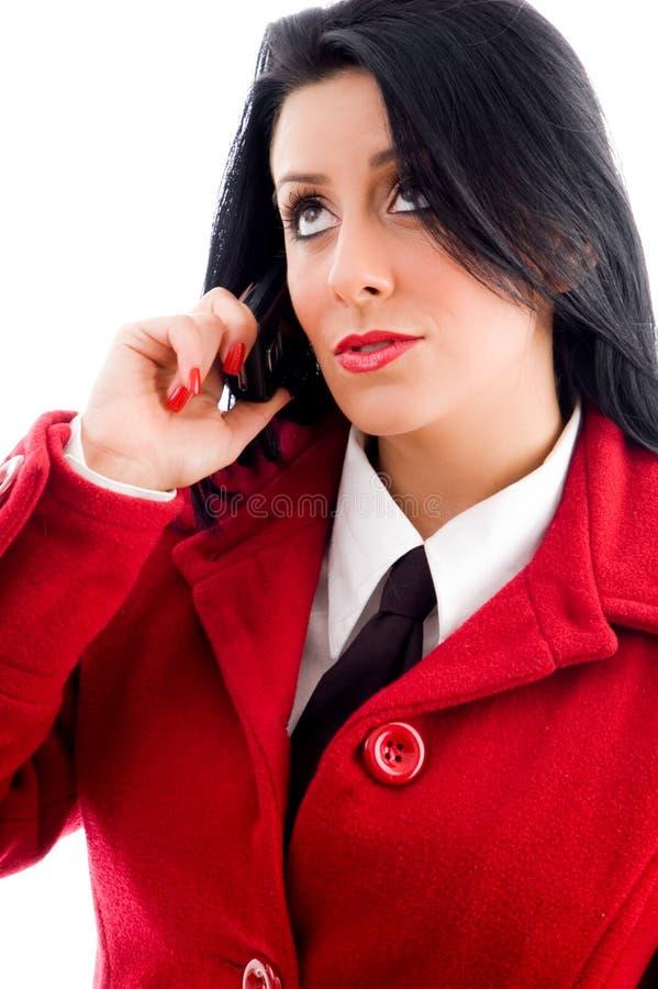 Mujer joven que habla en el teléfono y que mira hacia arriba