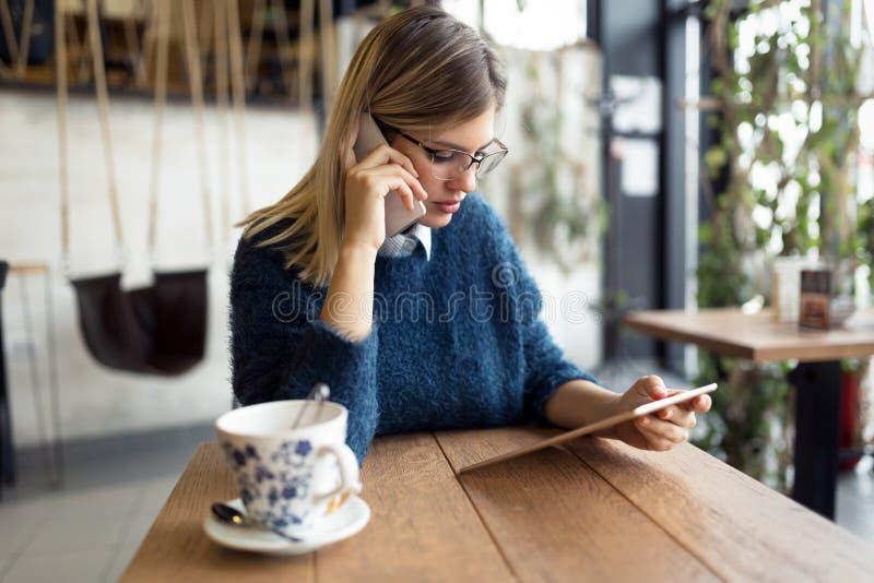 Mujer joven que habla en el teléfono y que usa la tableta foto de archivo