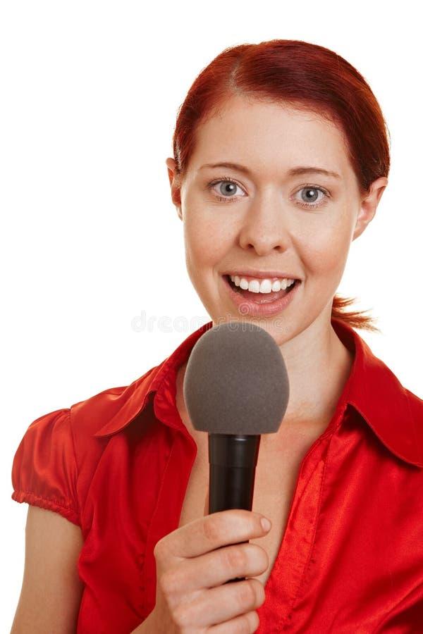 Mujer joven que habla en micrófono foto de archivo