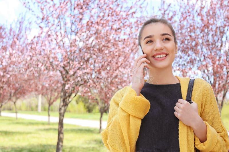 Mujer joven que habla por el teléfono al aire libre imagen de archivo libre de regalías