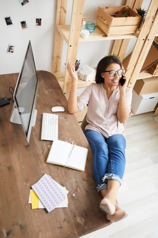 Mujer joven que habla por el teléfono en el escritorio fotos de archivo
