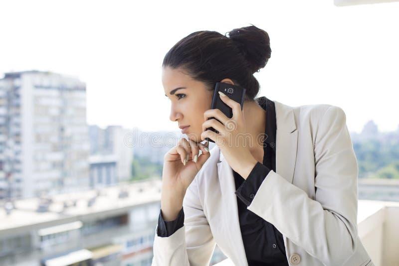 Mujer joven que habla sobre el teléfono fotos de archivo
