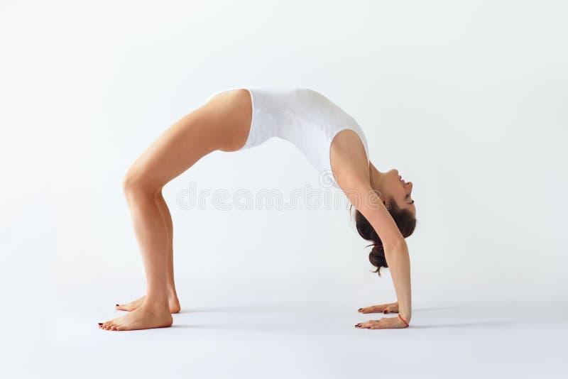 Mujer joven que hace actitud ascendente de la rueda del arco del asana de la yoga fotos de archivo