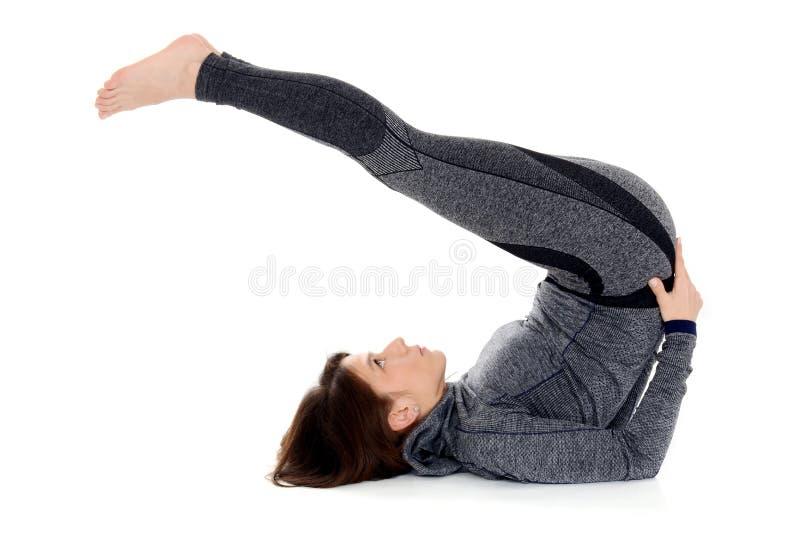 Mujer joven que hace actitud de la paleta de Halasana del asana de la yoga foto de archivo