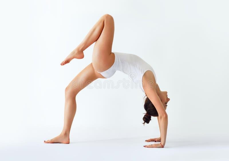 Mujer joven que hace actitud del puente del asana de la yoga con la pierna derecha para arriba fotos de archivo