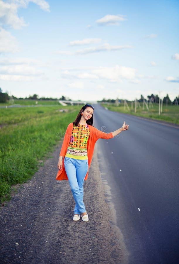 Mujer joven que hace autostop imagen de archivo