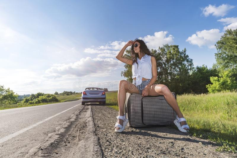 Mujer joven que hace autostop en un camino con el bolso del equipaje en los campos la muchacha se está sentando en equipaje y est fotos de archivo