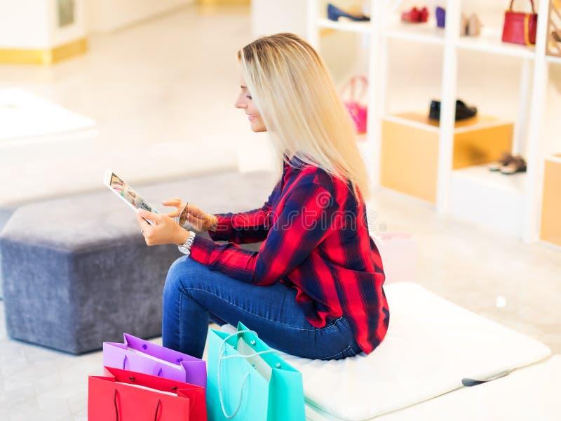 Mujer joven que hace compras en línea con la tableta y la tarjeta de crédito fotos de archivo