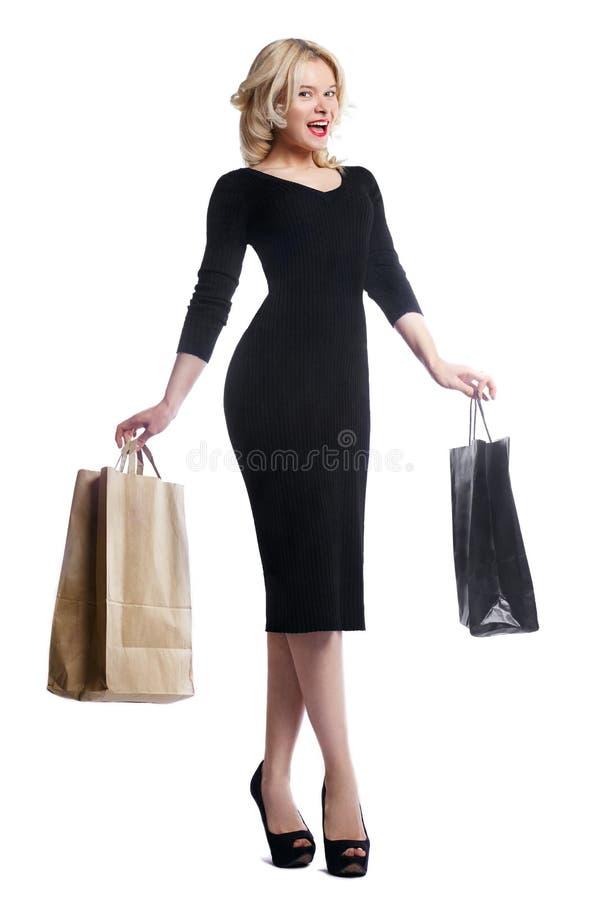 Mujer joven que hace compras que sostiene bolsos aislados en el fondo blanco del estudio Moda y ventas del amor Muchacha rubia fe fotografía de archivo libre de regalías