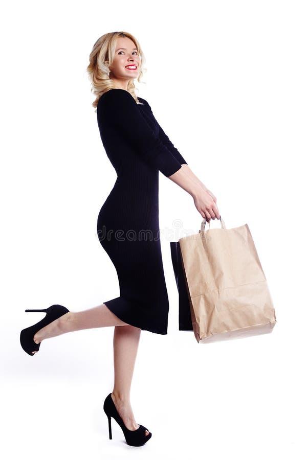 Mujer joven que hace compras que sostiene bolsos aislados en el fondo blanco del estudio Moda y ventas del amor Muchacha rubia fe fotografía de archivo