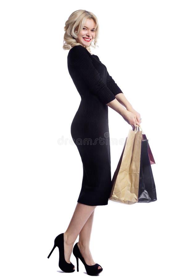 Mujer joven que hace compras que sostiene bolsos aislados en el fondo blanco del estudio Moda y ventas del amor Muchacha rubia fe fotos de archivo