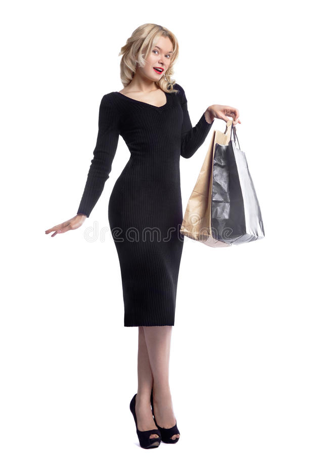 Mujer joven que hace compras que sostiene bolsos aislados en el fondo blanco del estudio Moda y ventas del amor Muchacha rubia fe imagen de archivo